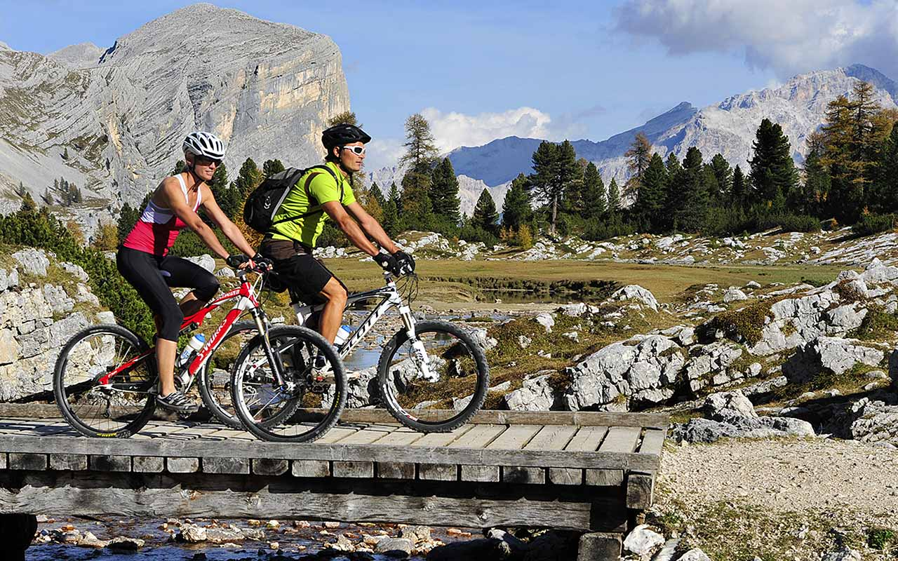 Two boys on a bike cross a wooden bridge and in the background the Dolomites
