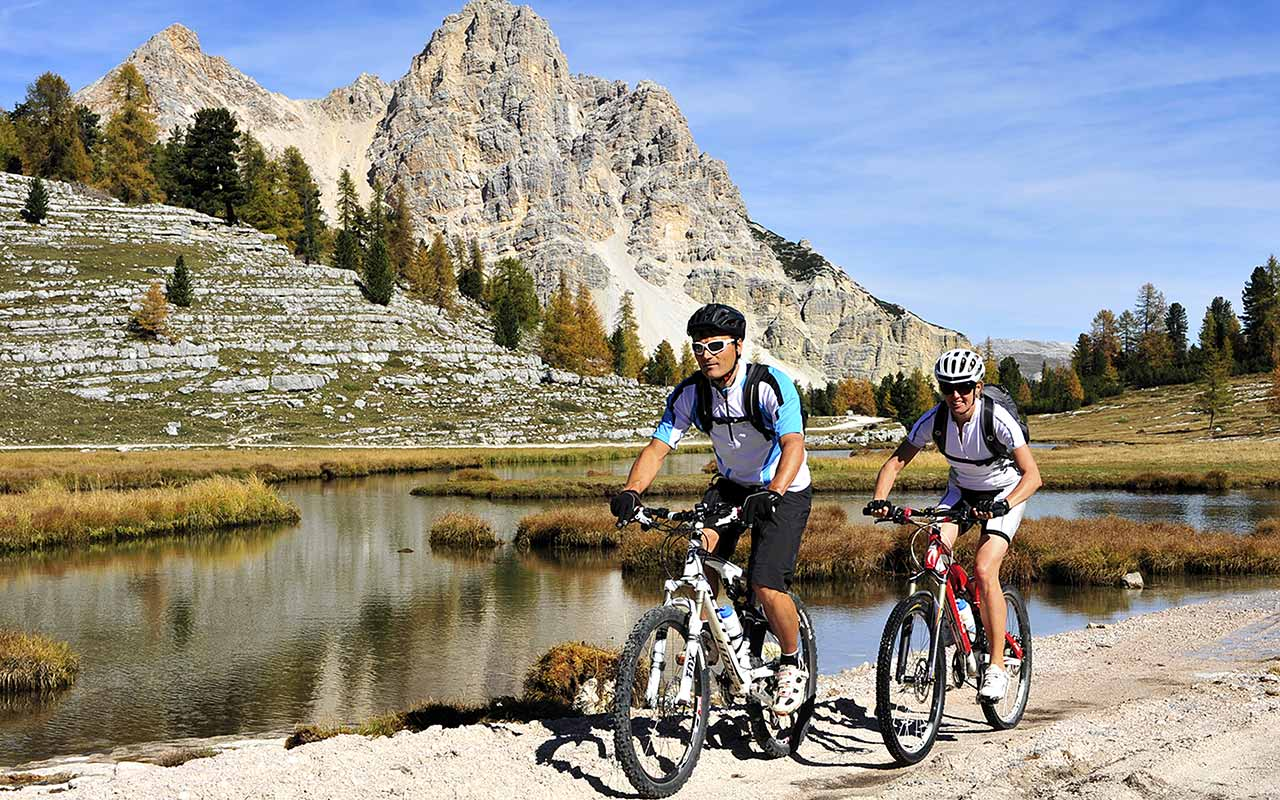 Cyclists ride along a mountain lake on the Alpe di Fanes
