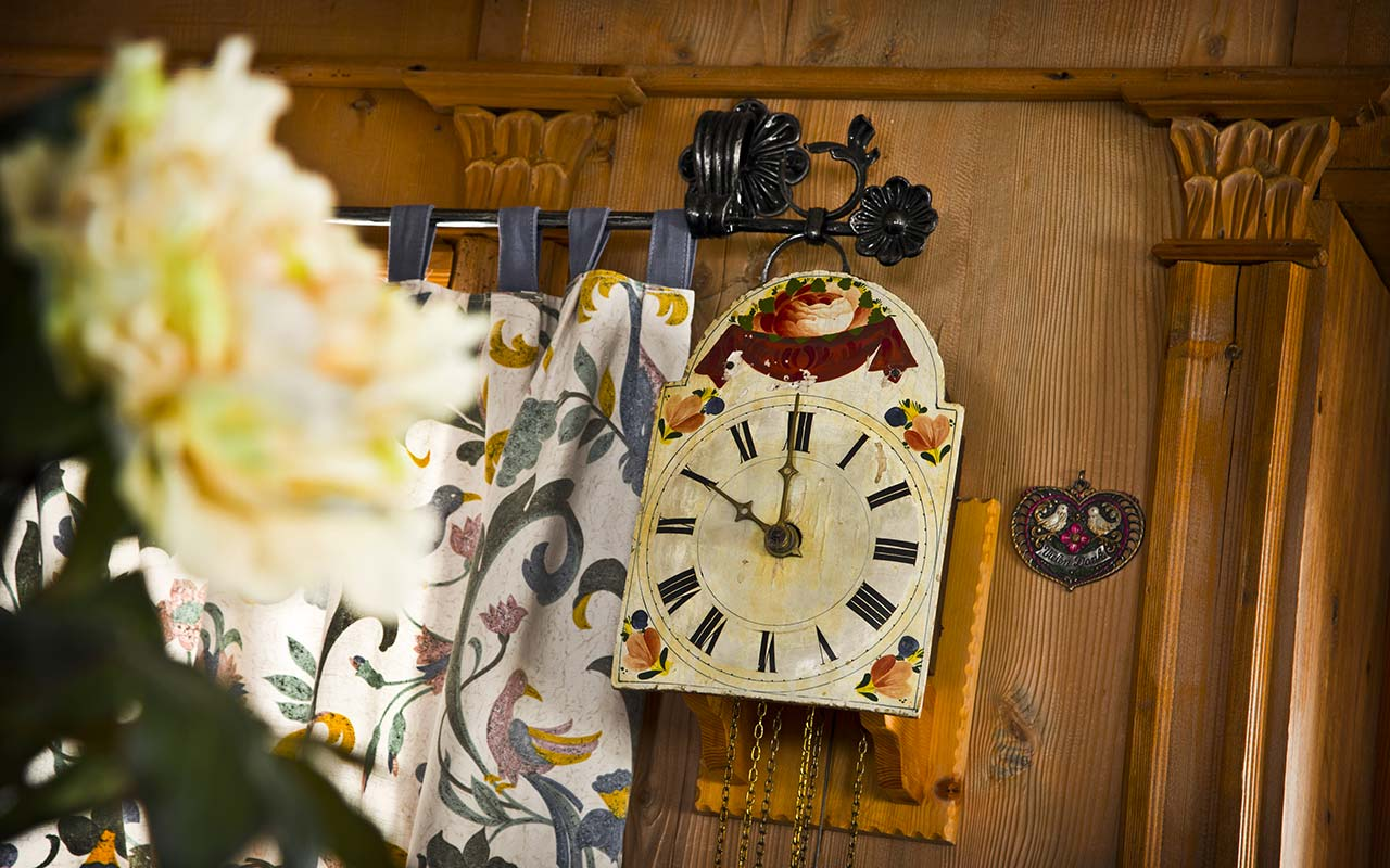 Detail of an old clock with flowers on a wooden wall